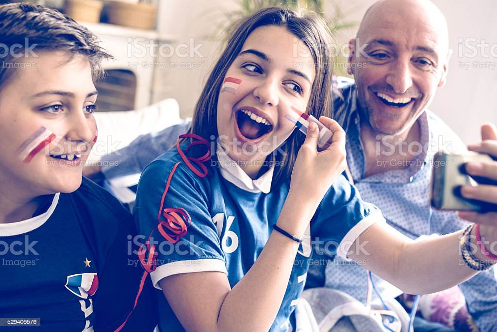 french family in soccer fan outfit taking selfie stock photo