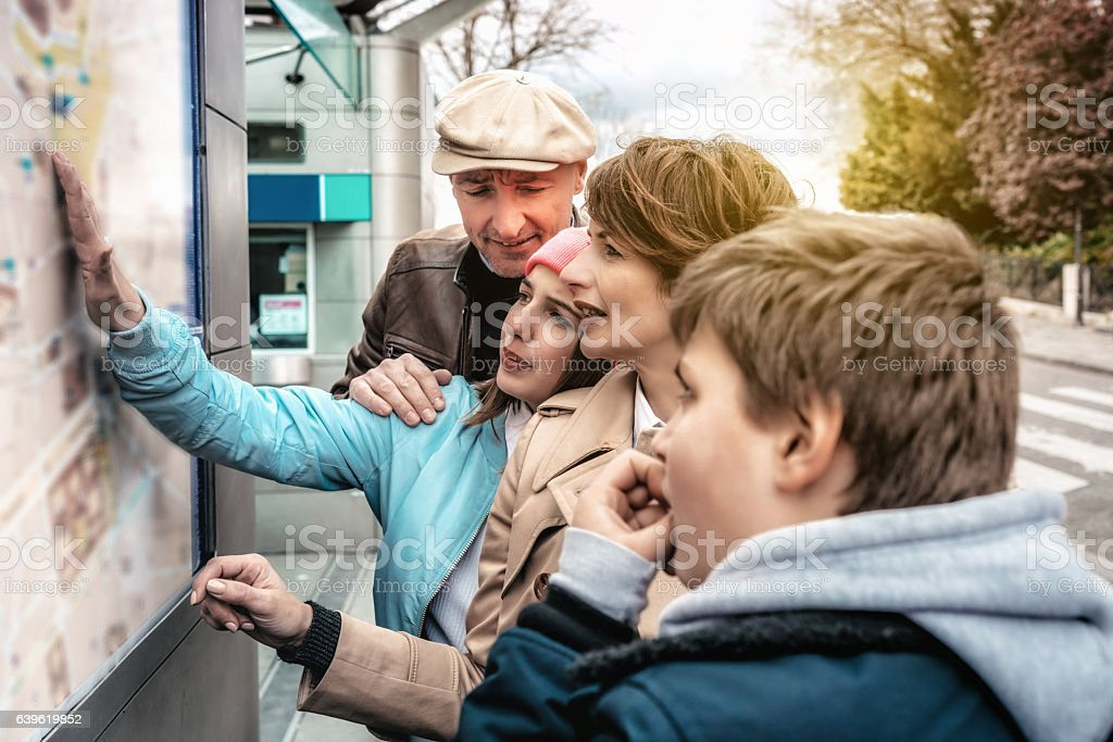 french family looking at outdoor city map in monmartre  Paris stock photo