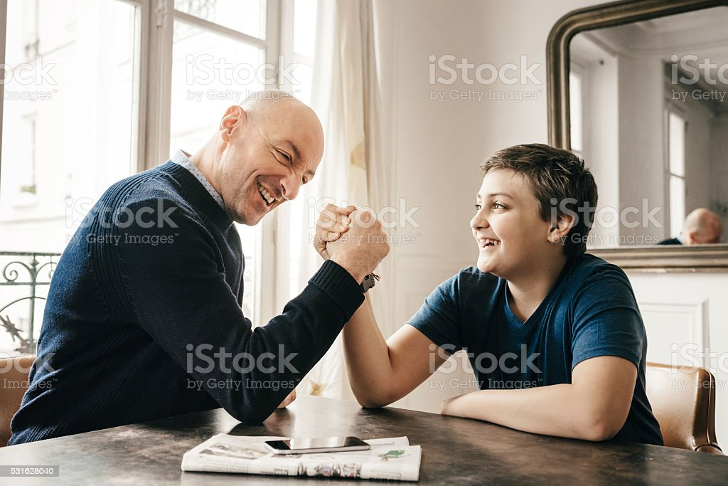 french father and his son doing arm wrestling on table stock photo