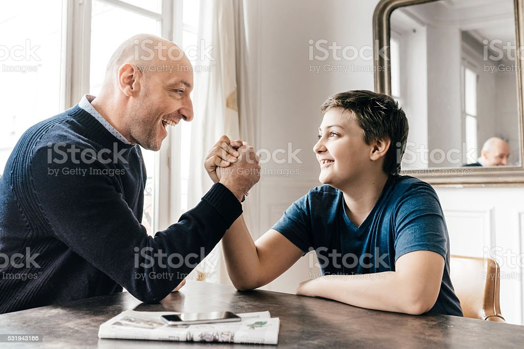 french father and his son doing arm wrestling stock photo