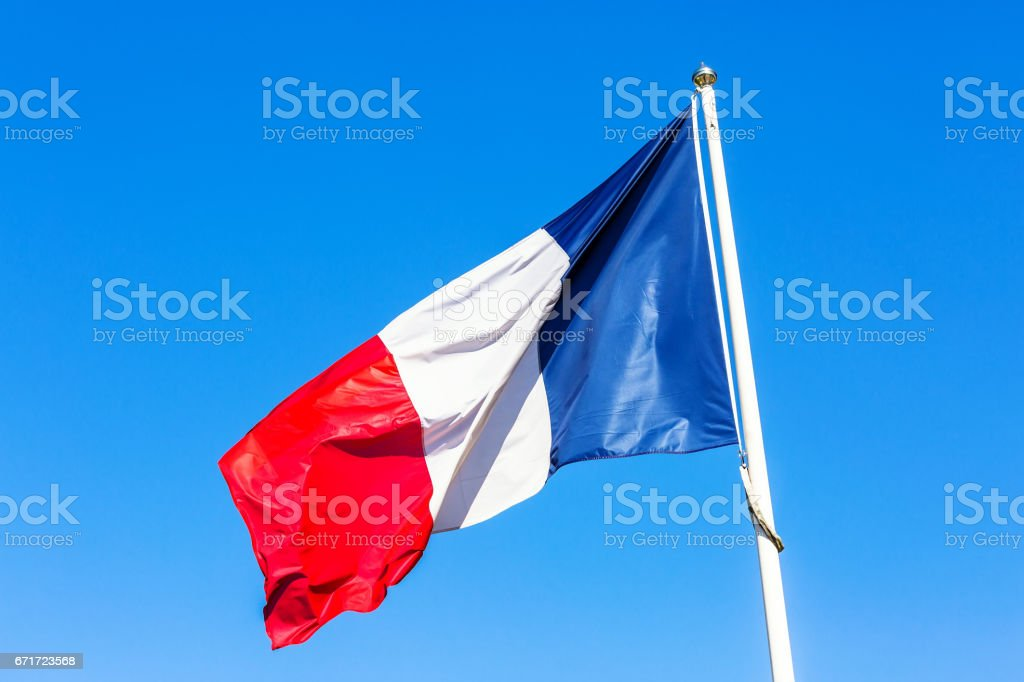 French flag under blue sky stock photo