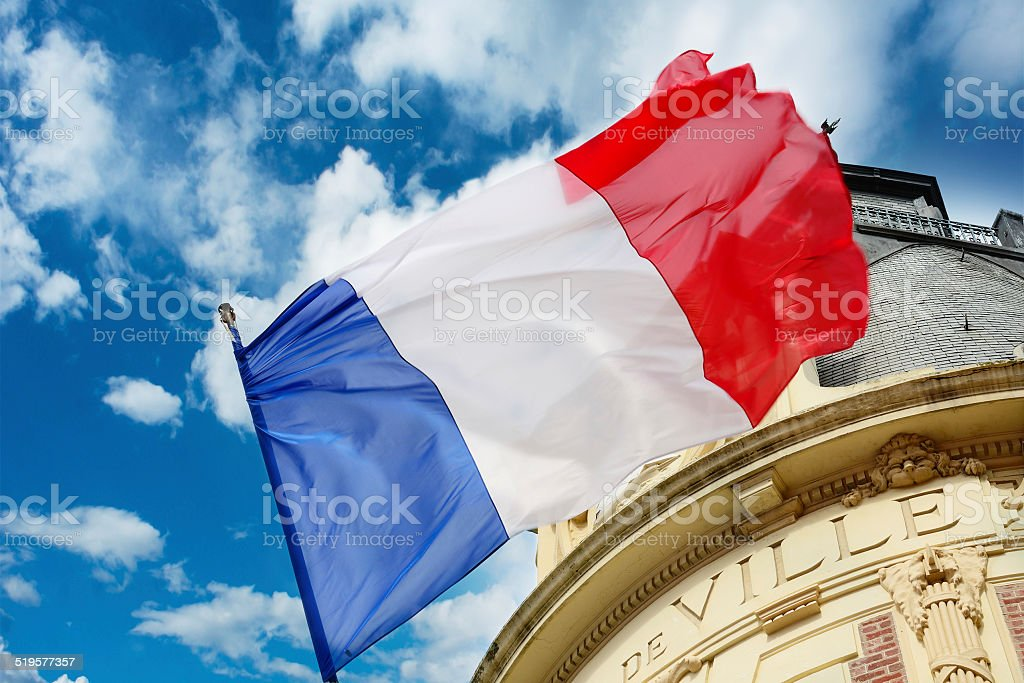 French flag waiving over some Hotel de Ville stock photo