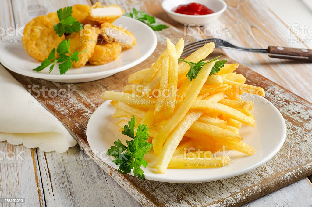 French fries and chicken nuggets on   wooden table stock photo