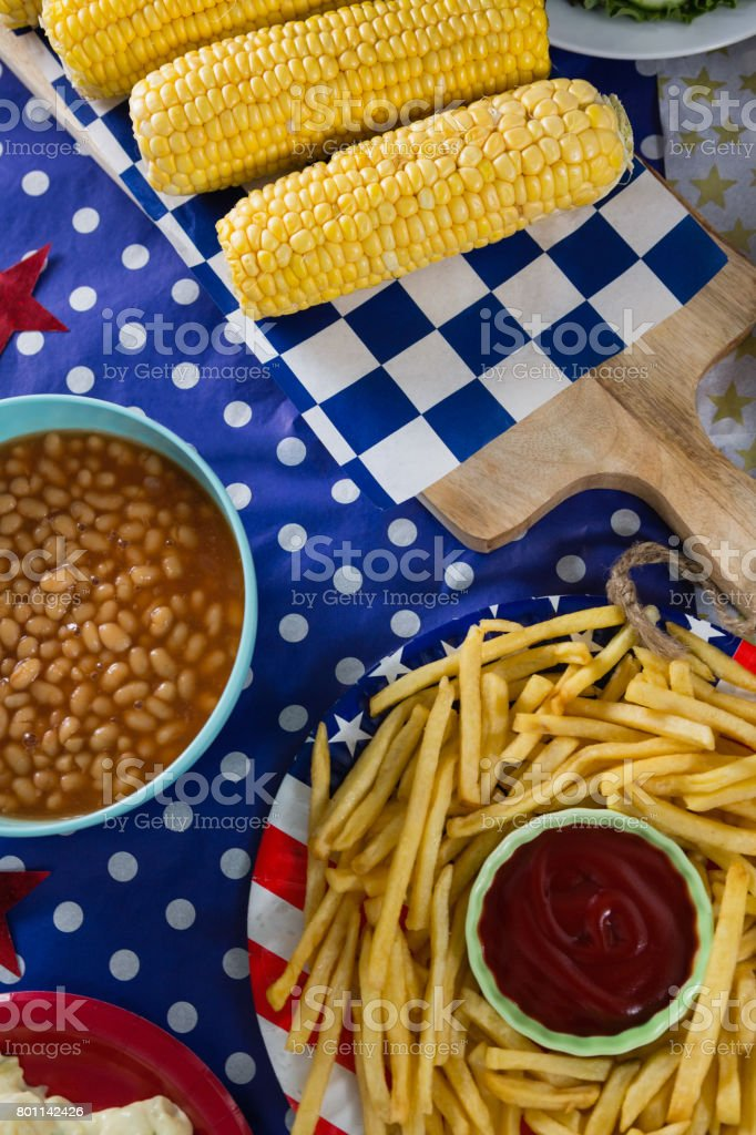 French fries and corn cob on wooden table with 4th july theme stock photo
