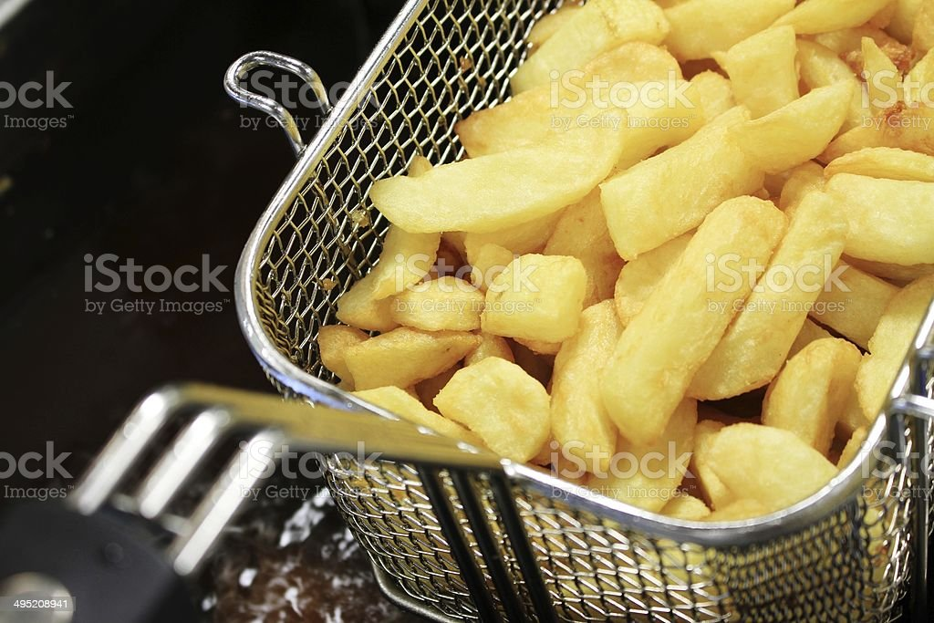 french fries and fish in frying baskets stock photo