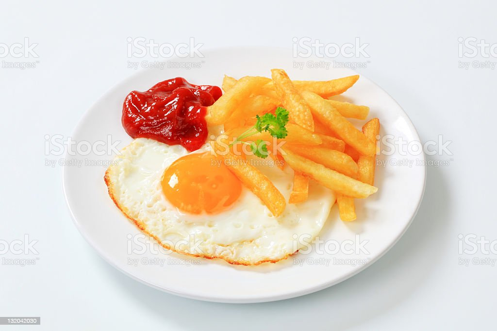 French fries, fried egg and ketchup stock photo