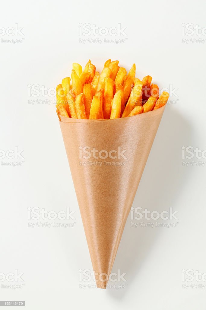 French fries in a paper cone stock photo