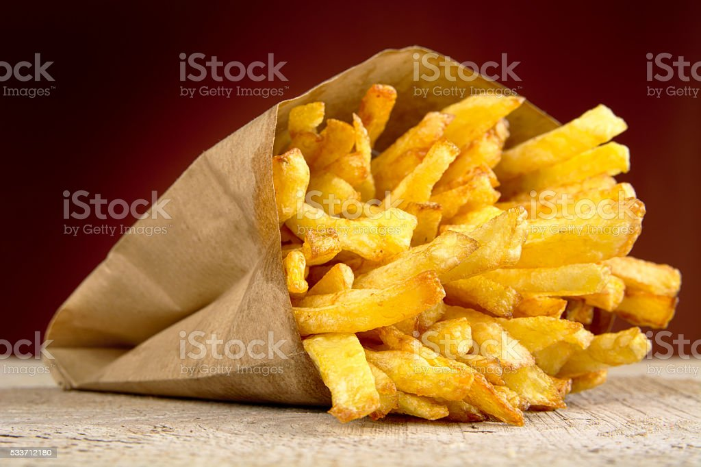 French fries in bag on burned background on wooden table stock photo