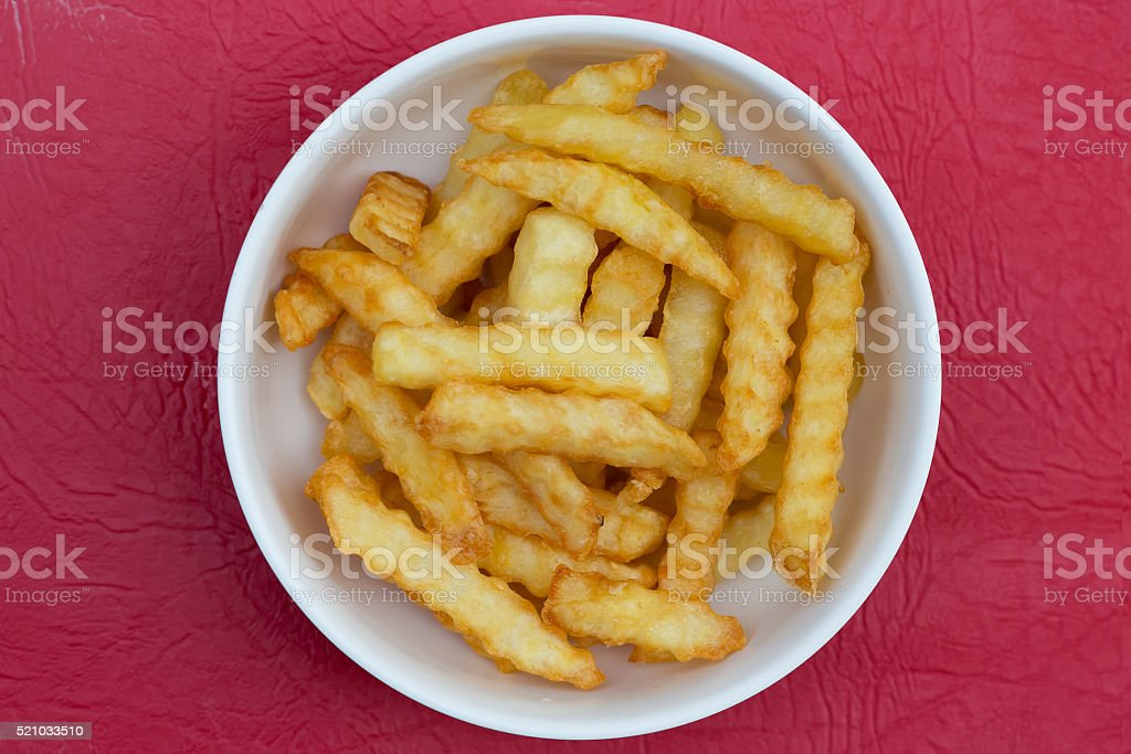 French fries in bowl on red leather floor stock photo