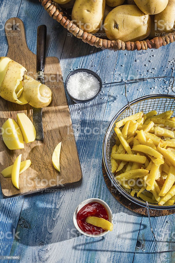 French fries made from potatoes on blue table royalty-free stock photo