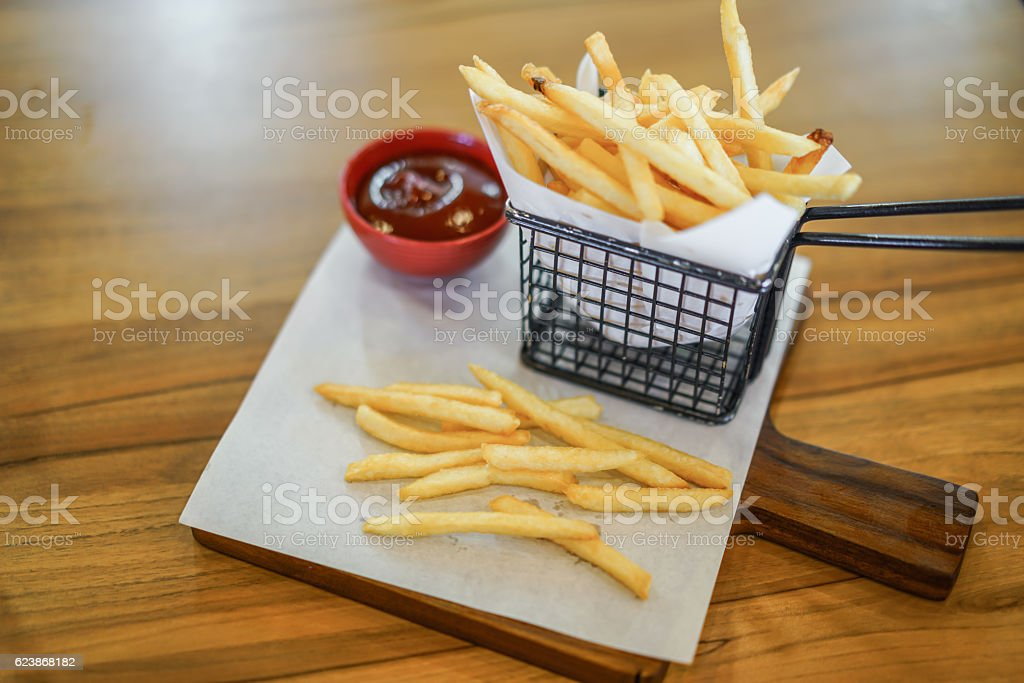 French fries on wooden table stock photo