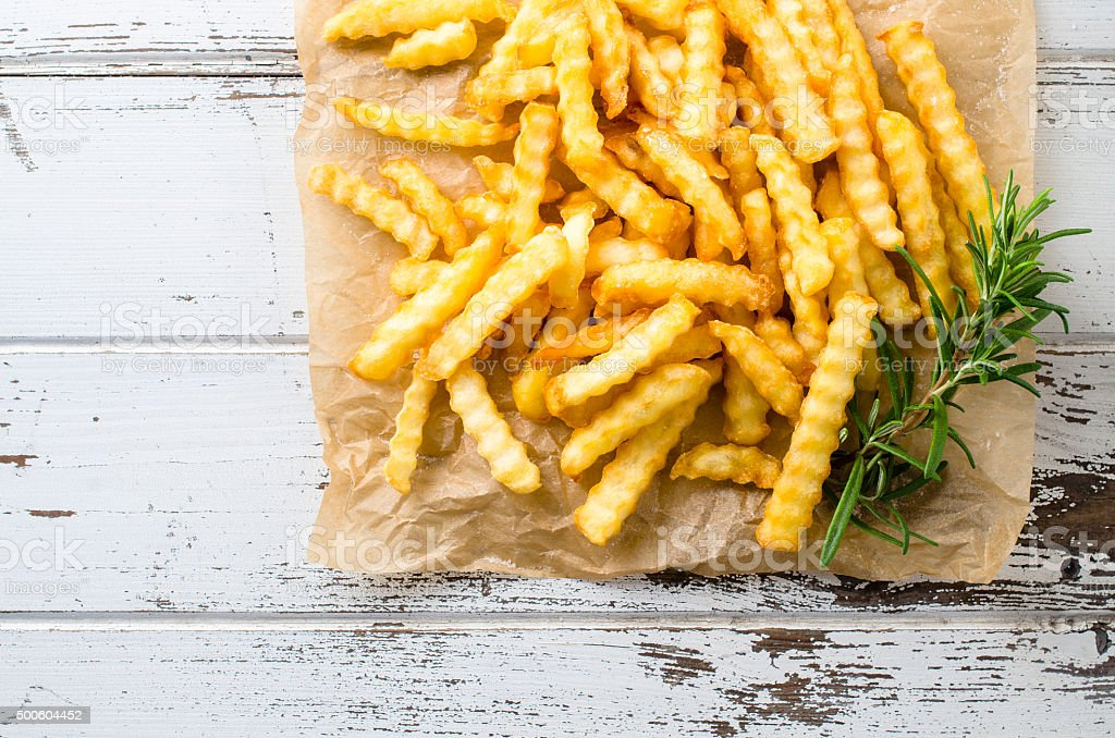 French fries over old wooden table stock photo