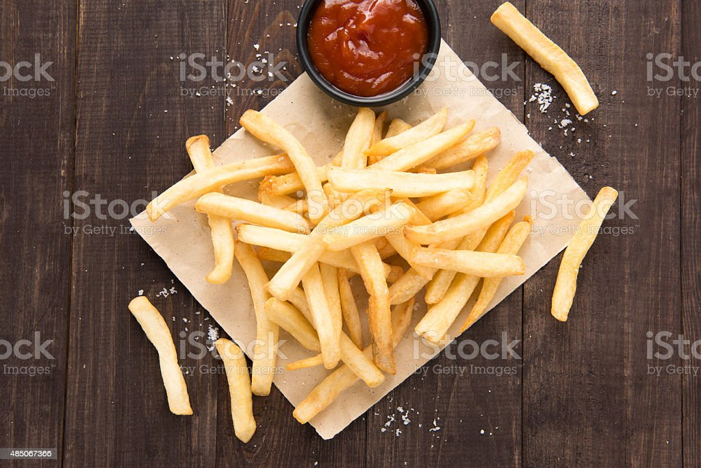 French fries with ketchup on wooden background stock photo