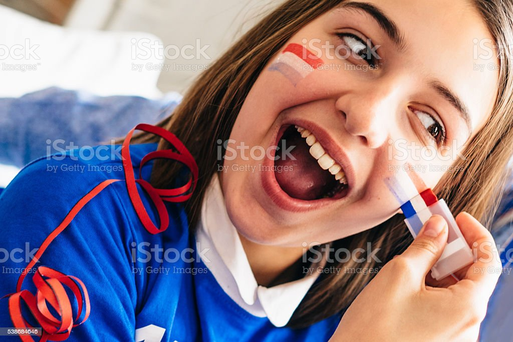 french girl soccer fan making face painting with french colors stock photo