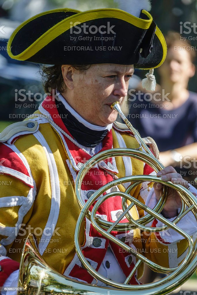 French horn player in mock 18th-century military encampment stock photo