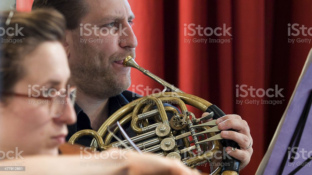 French Horn player in orchestra stock photo