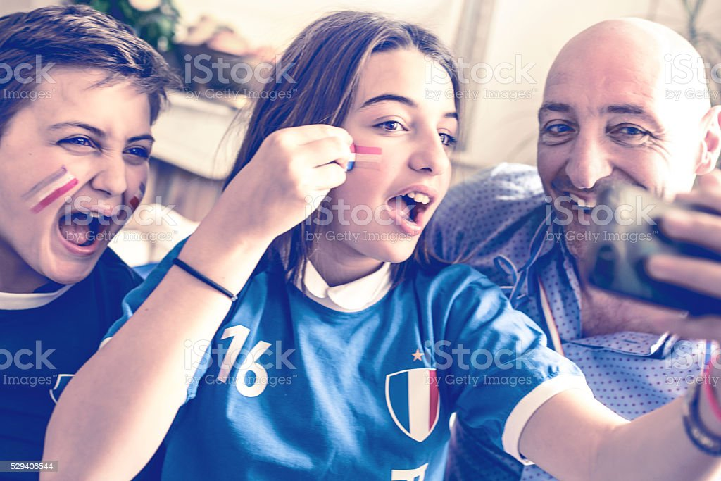 french kids  in soccer fan outfit and father taking selfie stock photo