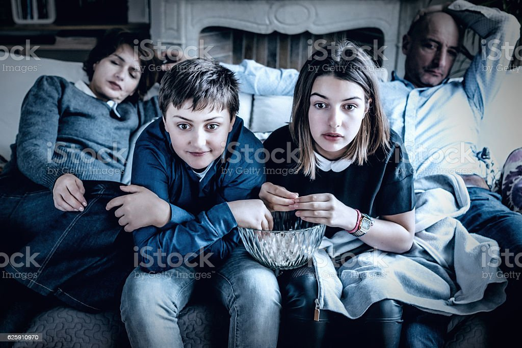 french kids watching thrilling tv on sofa while parents sleeping stock photo