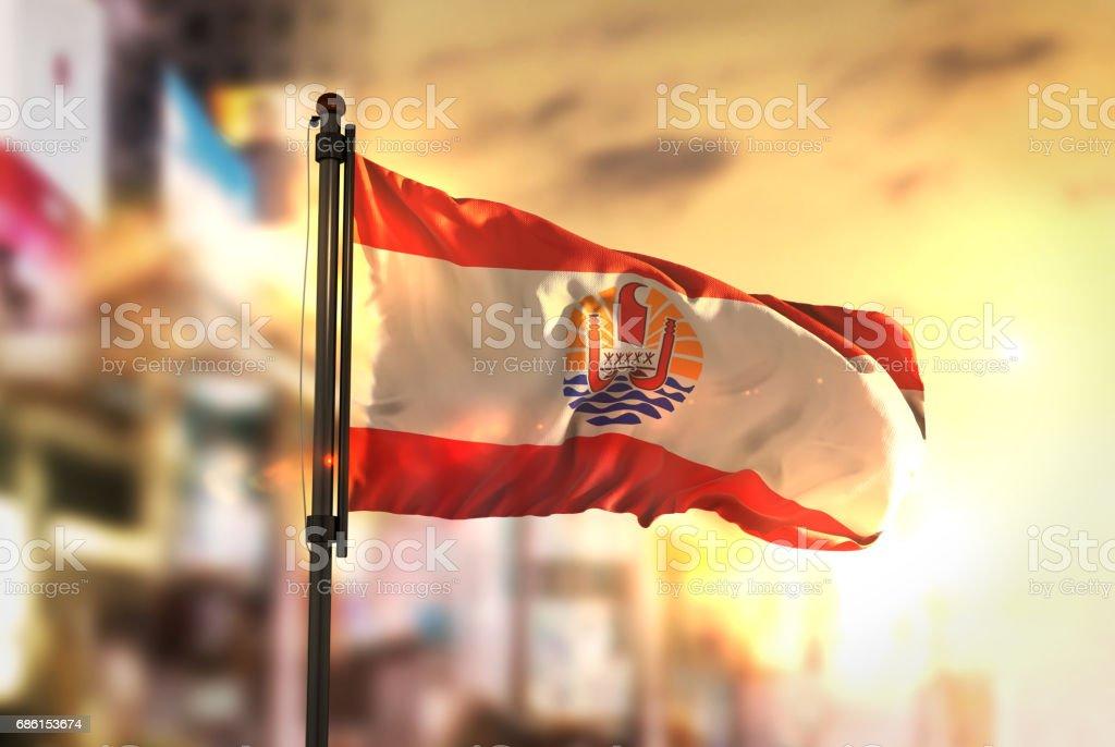French Polynesia Flag Against City Blurred Background At Sunrise Backlight stock photo