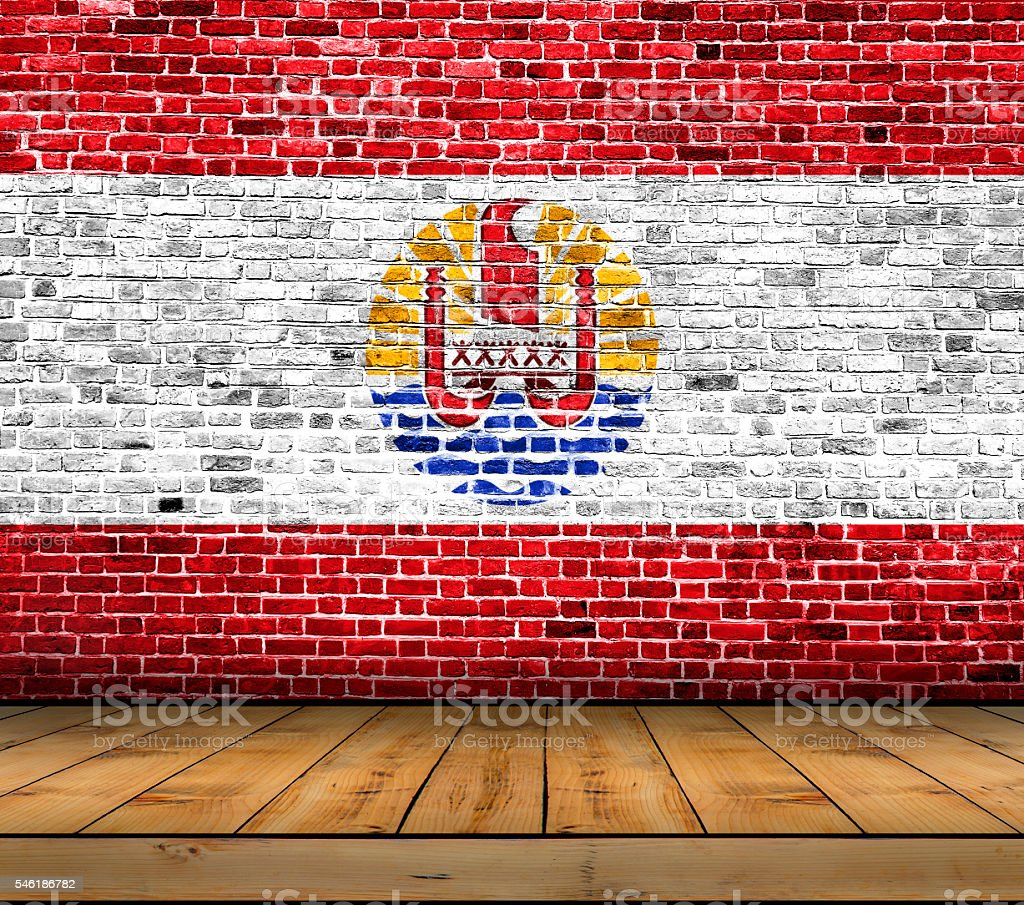 French Polynesia flag painted on brick wall with wooden floor stock photo