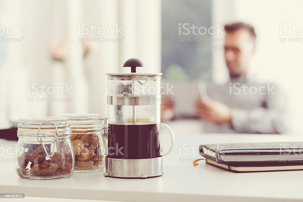 French press coffee maker and cookies with a defocused man stock photo
