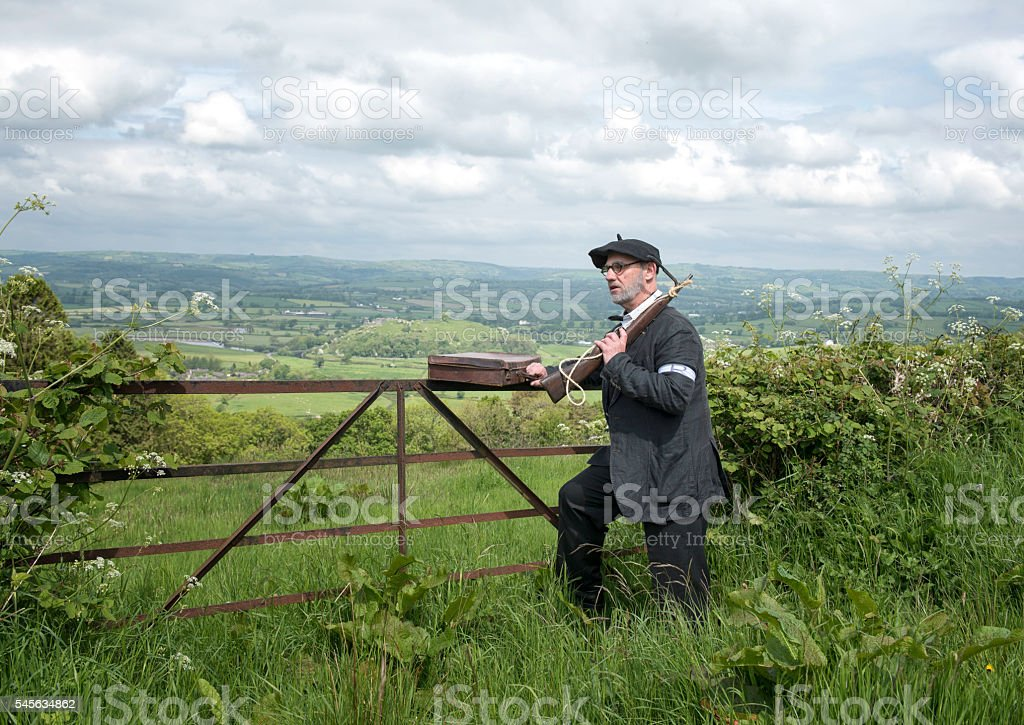 French Resistance soldier with rifle and briefcase, overlooking green fields stock photo