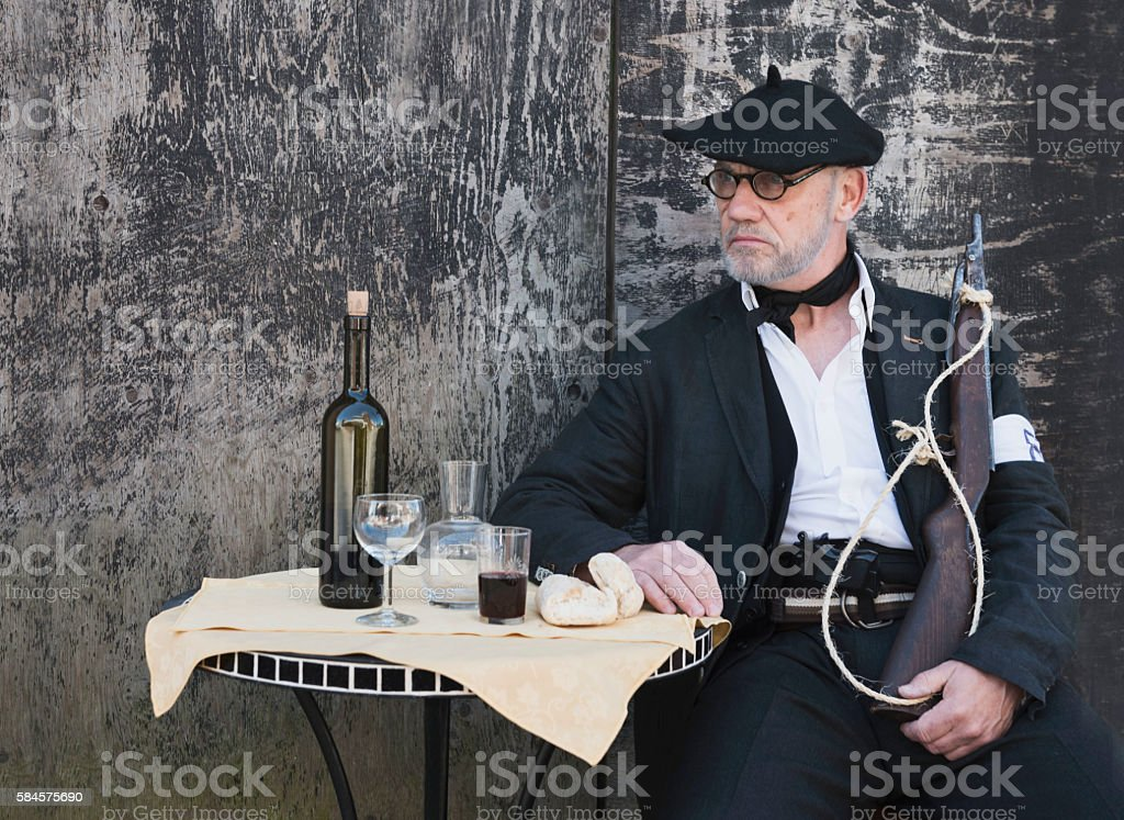 French Resistance soldier with rifle, sitting at a table stock photo