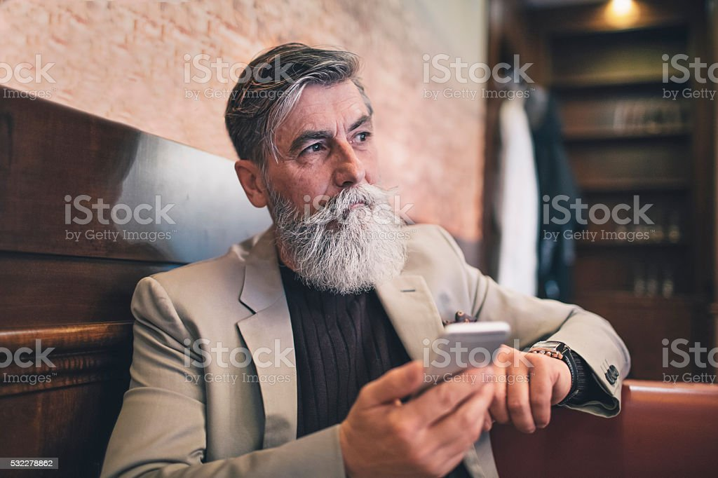 French senior man using a mobile phone stock photo
