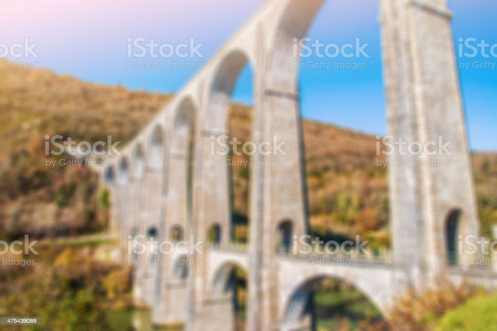 French stone viaduct in autumn season blurred by focus stock photo