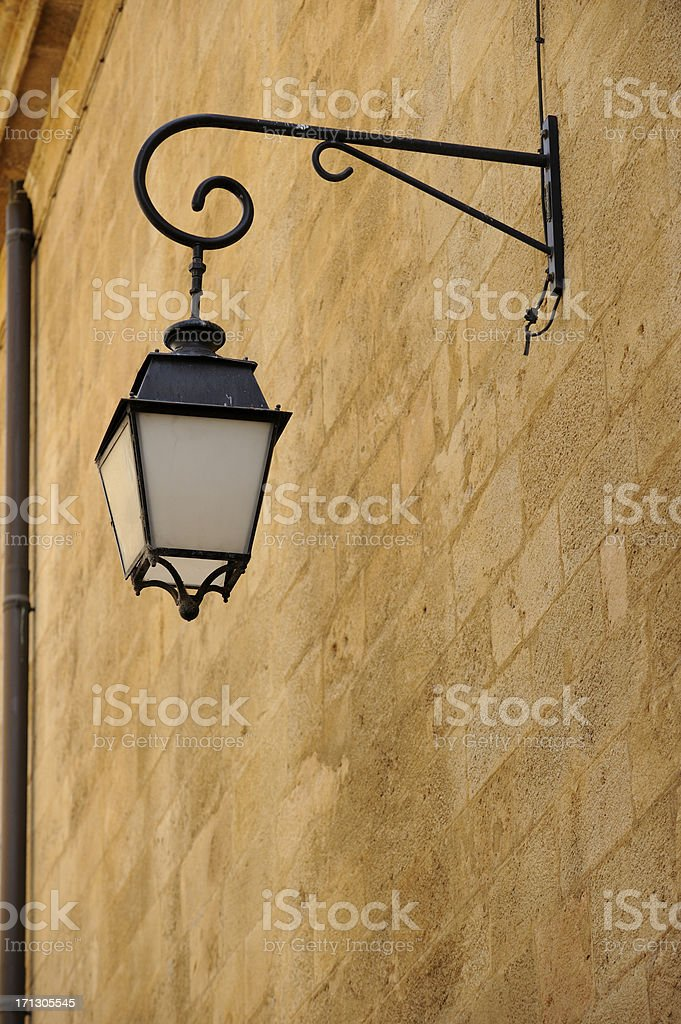 French street lamp against plain wall stock photo