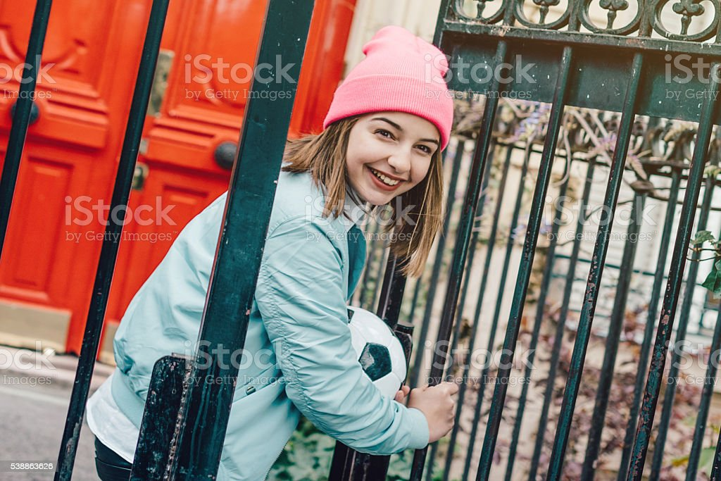 french teenage girl with football at iron gate in paris stock photo