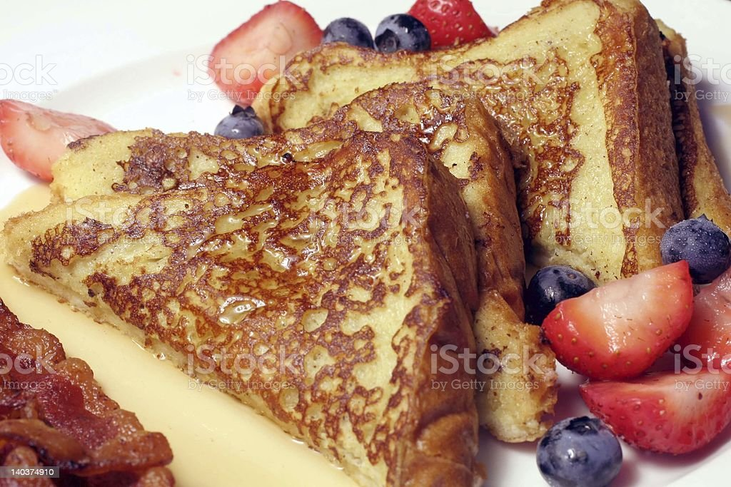 French toast and syrup with a side of bacon and fruit stock photo