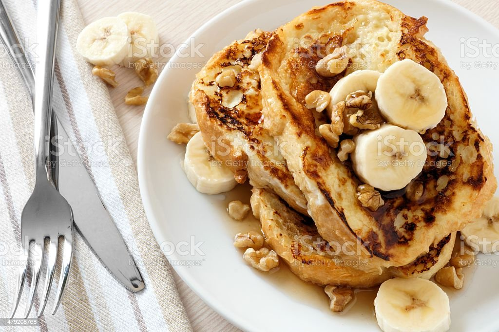 French toast with bananas, walnuts and maple syrup stock photo