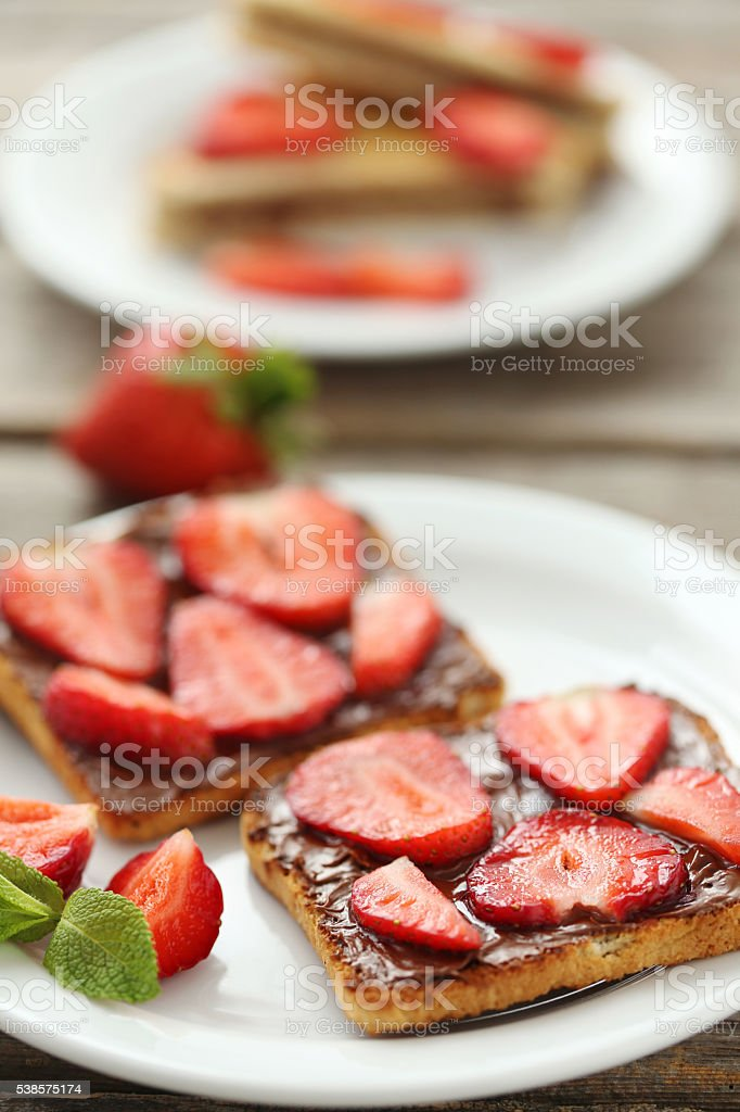 French toasts with chocolate and strawberry on wooden table stock photo