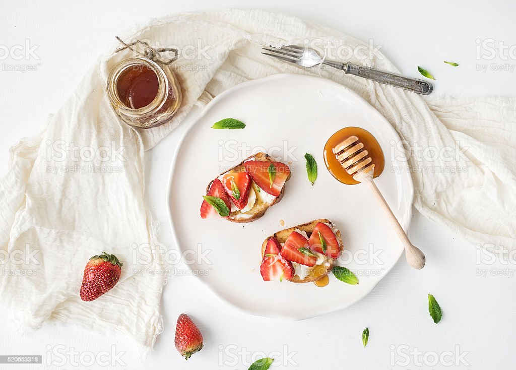 French toasts with strawberry, cream cheese, honey and mint on stock photo