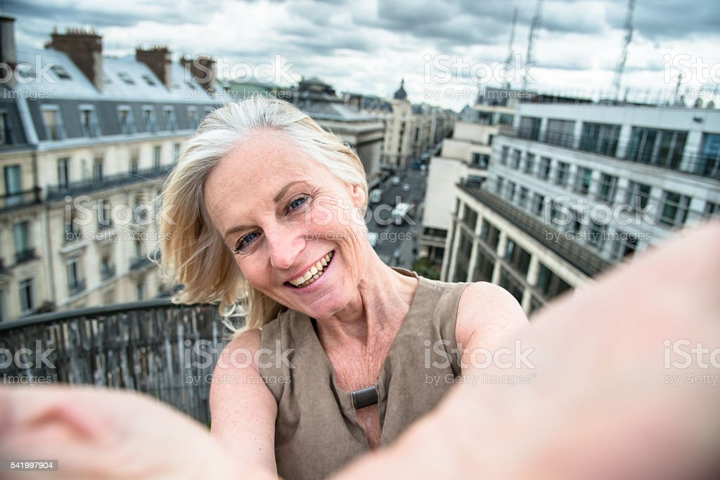 french woman take a selfie on the rooftop in paris stock photo