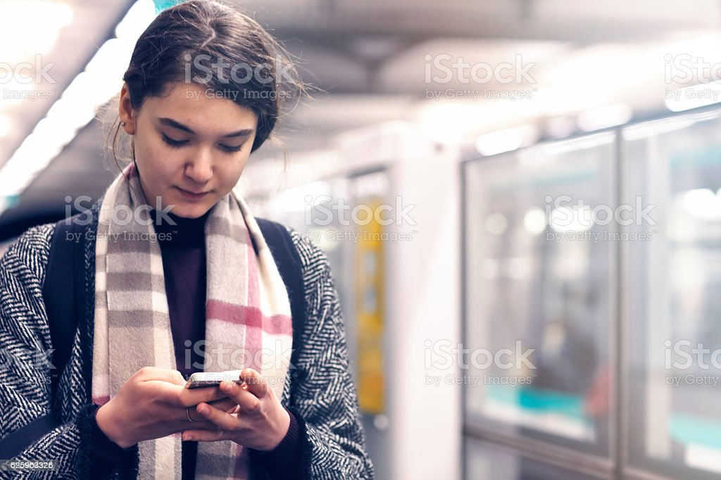 French woman using a smartphone on the metro subway station stock photo