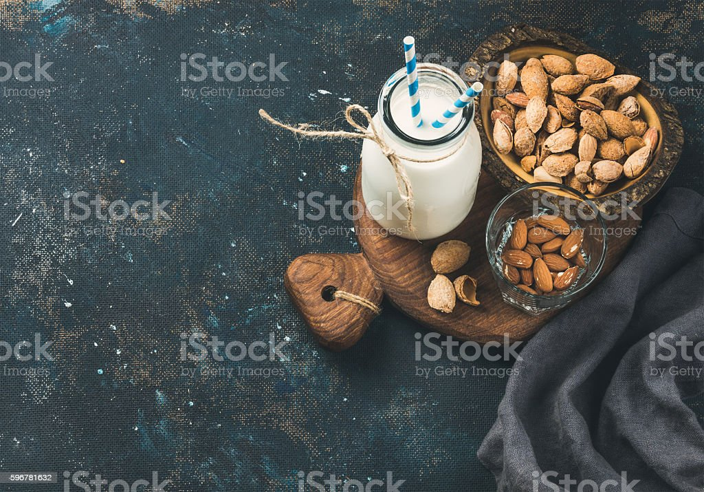 Fresh almond milk in glass bottle with almonds in bowls stock photo