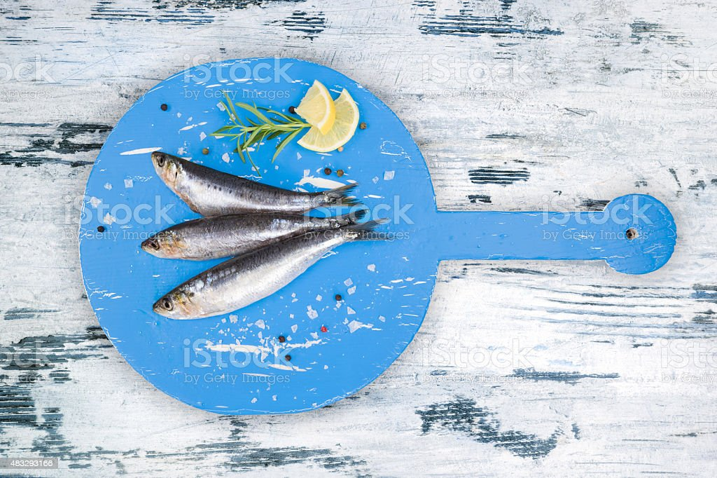 Fresh anchovy fish on white and blue wooden kitchen board. stock photo