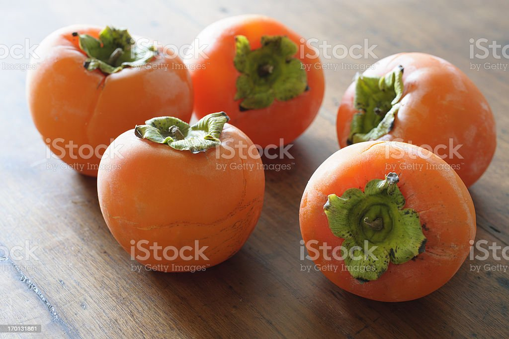 Fresh and Ripe Persimmon fruit backlit on old wooden table stock photo