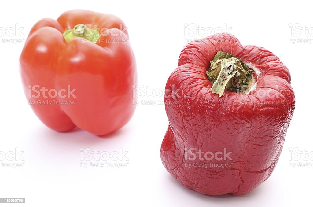 Fresh and wrinkled peppers on white background royalty-free stock photo