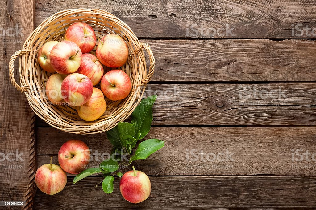 fresh apples in wicker basket on wooden table stock photo