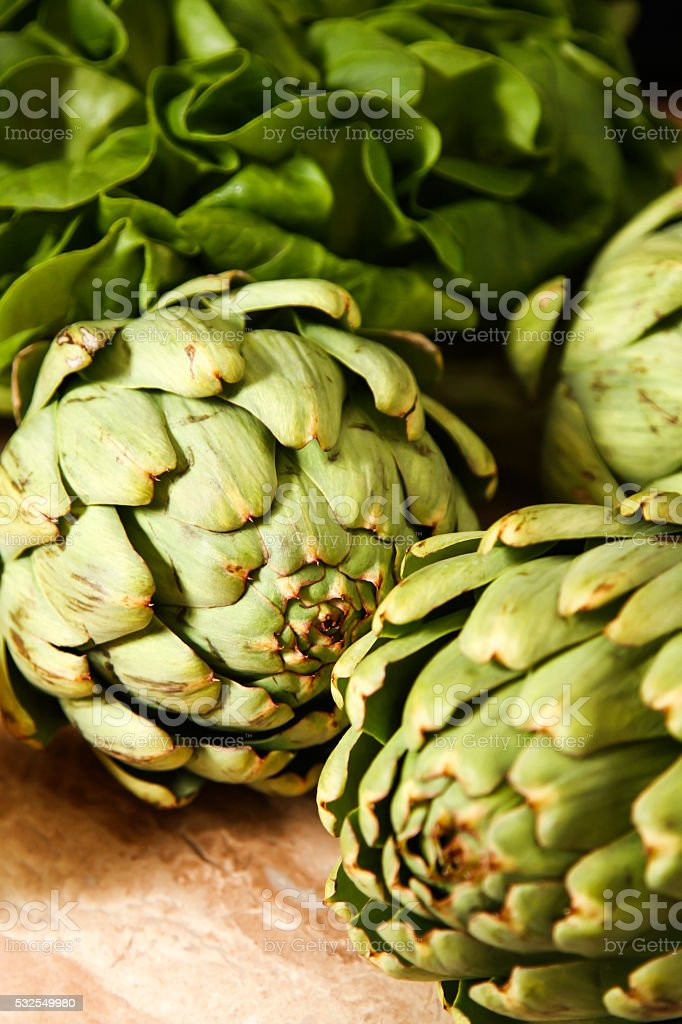 fresh artichokes on rustic wooden background stock photo