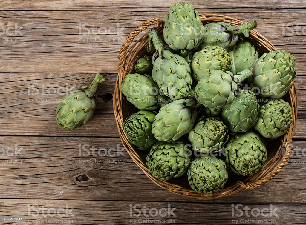 Fresh artichokes on wood, top view. stock photo