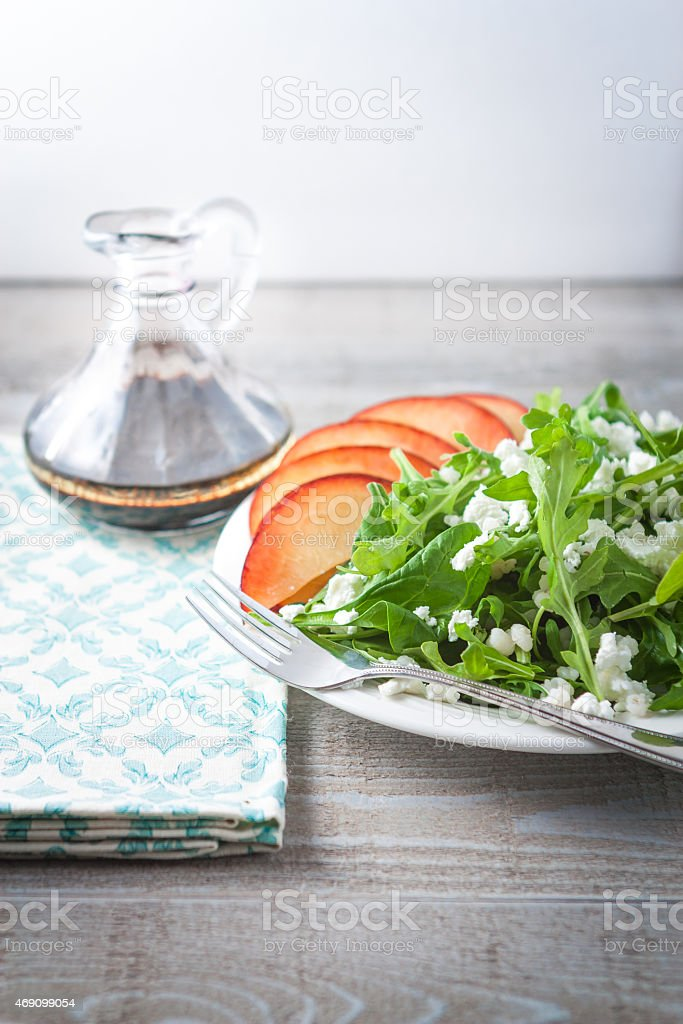 Fresh Arugula and Spinach Salad with Nectarine on Table stock photo