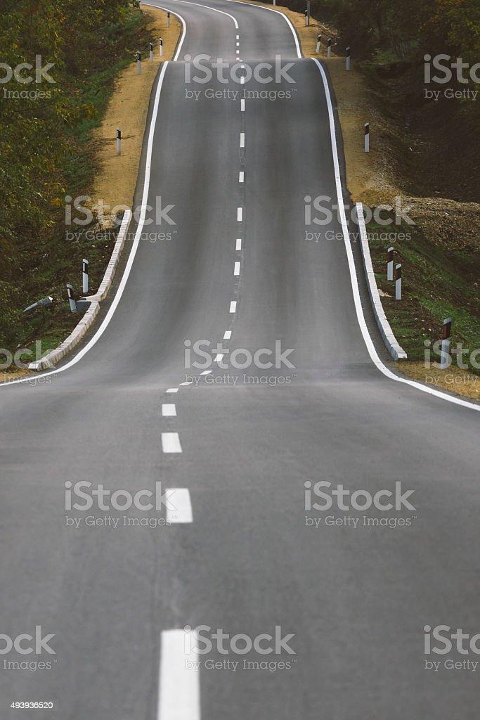 Fresh asphalt road over hills stock photo