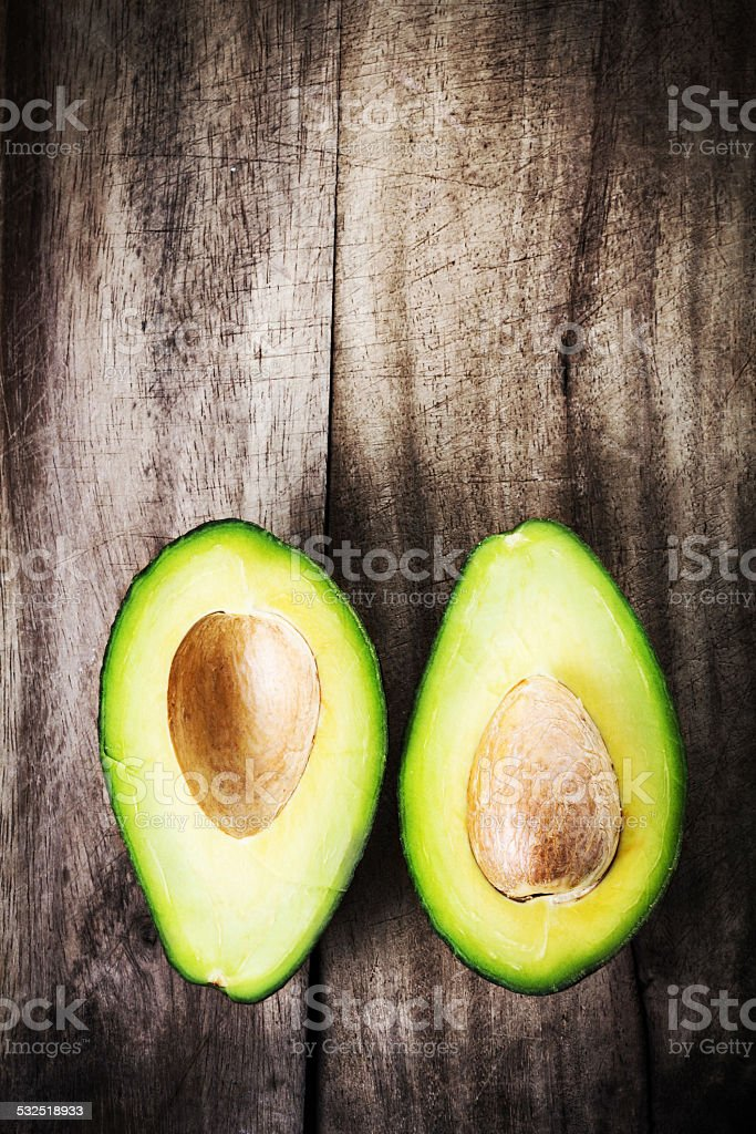 Fresh Avocado sliced over vintage wooden background close up. stock photo