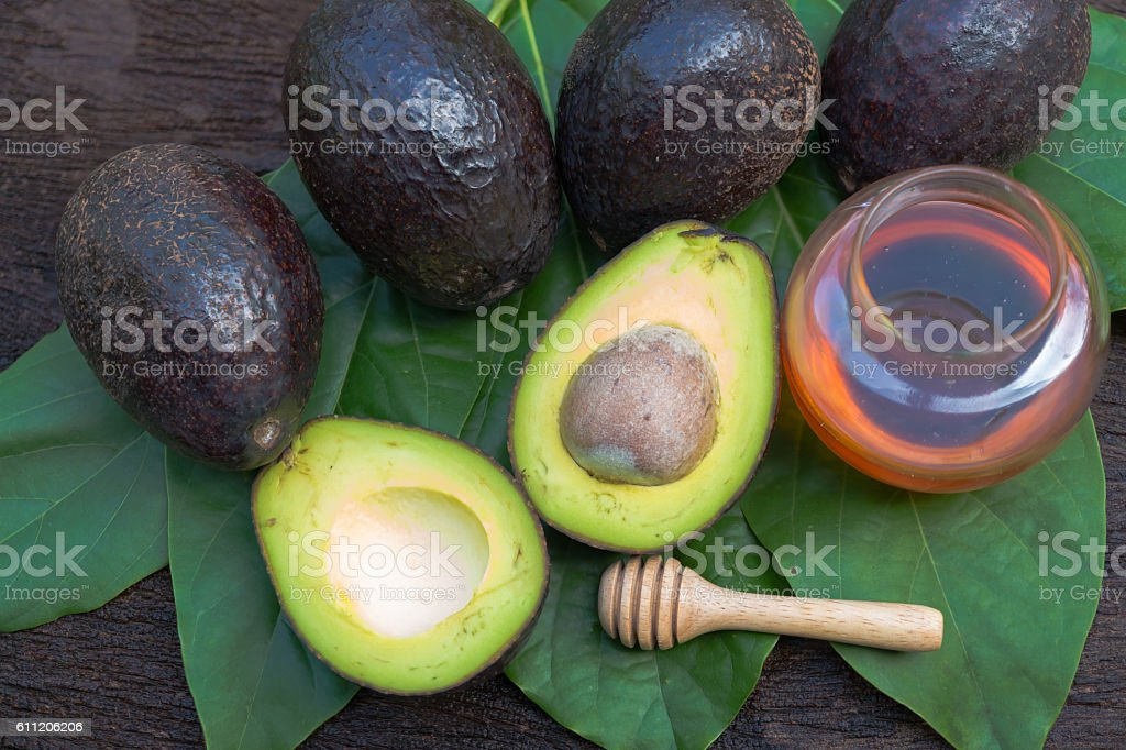Fresh avocado with  honey on wooden background stock photo