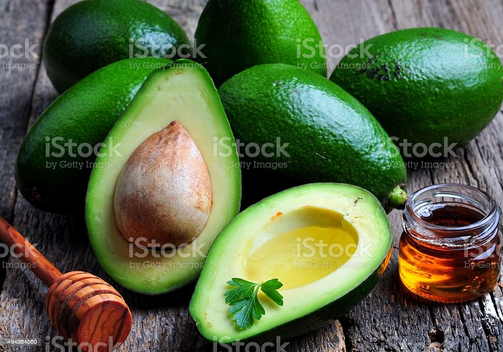 Fresh avocado with olive oil and honey on wooden background stock photo