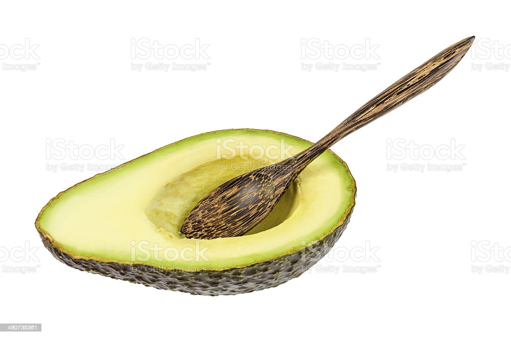 Fresh avocado with wooden spoon isolated royalty-free stock photo